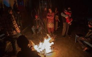 Residents spend the night by a fire in a open space inside a school on April 26, 2015 in Kathmandu, Nepal.